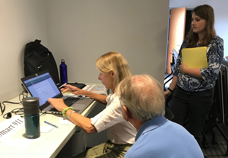 UD student Christine Hoh helped seniors register for the Smart 911 system at a workshop led by Coastal Hazards Specialist Danielle Swallow.