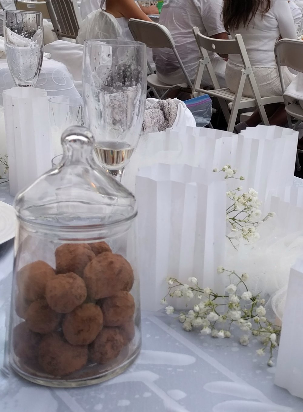 Decorating the table with food and flowers (without greenery - just sprigs of baby's breath tucked among tulle pompoms and vellum shades over candles.