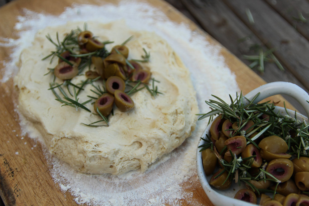 3. Roughly chop your olives and strip the leaves off the sprigs of rosemary. On a well floured surface flatten out your dough, sprinkle a handful of rosemary and olives, then fold in the edges; repeat this until all have been added to the loaf. Leave the bread to rise for 30 minuets or ideally up to 2 hours.  -