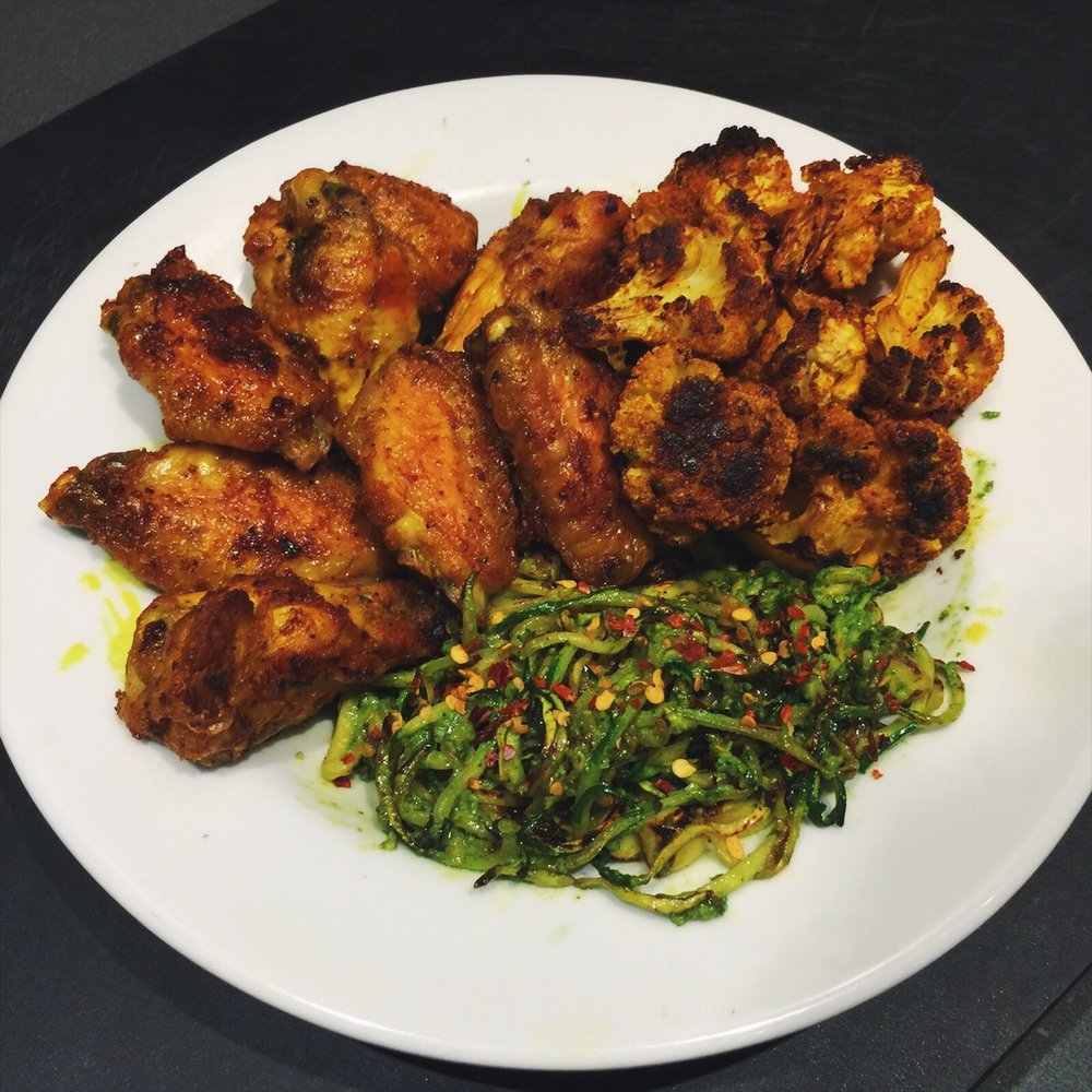 Crispy oven baked chicken wings, charred turmeric cauliflower, and pesto noodles with chilli.