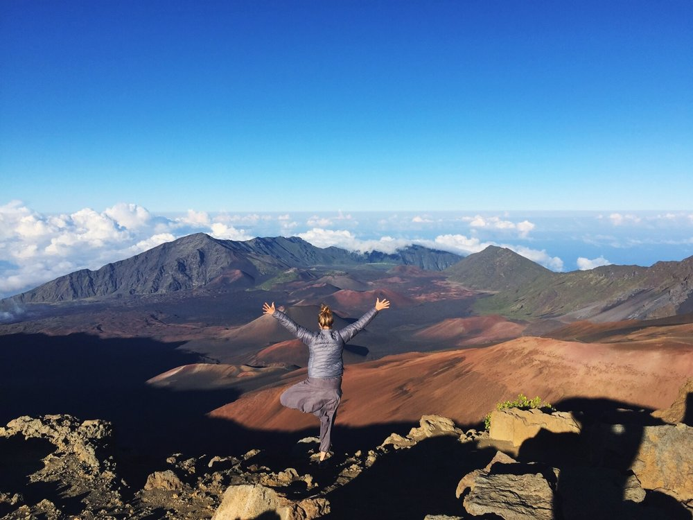 Tree pose 10,000ft above sea level, looking into the volcanic crater on top of Mt. Haleakala, on Maui, Hawaii.