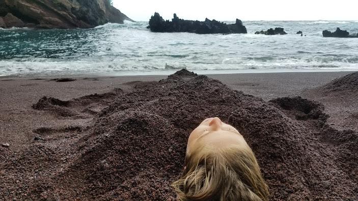 Buried in red sand in Hana, Maui, Hawaii.