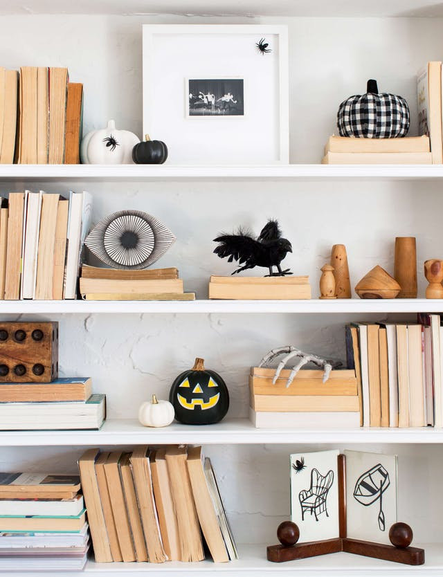 Simplicity - Your home doesn't have to look like the Great Pumpkin has taken over. Pick and theme, and stick to it! We're loving this neutral bookshelf with the understated Halloween items.