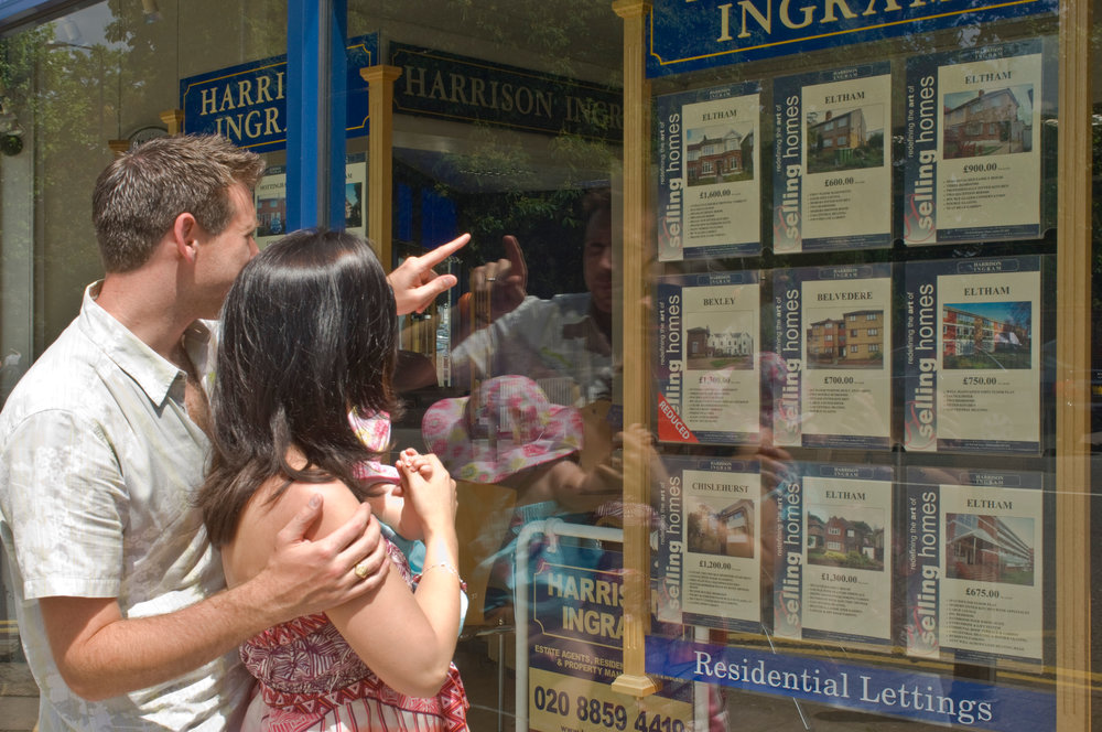 Young couple looking in estate agent window