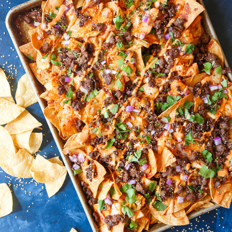 Korean Beef Nachos - We're always looking for unique recipes that will dazzle guests! Mmm, this dish is packed with worldly flavours: Korean-seasoned beef, caramelized kimchi, and Sriracha mayo drizzle. We're already reaching for seconds! Don't forget to top these off with melted cheese, onions, and sesame seeds.Get the Recipe