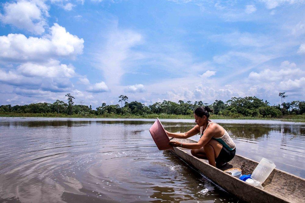 Gisela en la orilla del río cuando el agua está muy cerca de la casa durante la temporada de lluvias