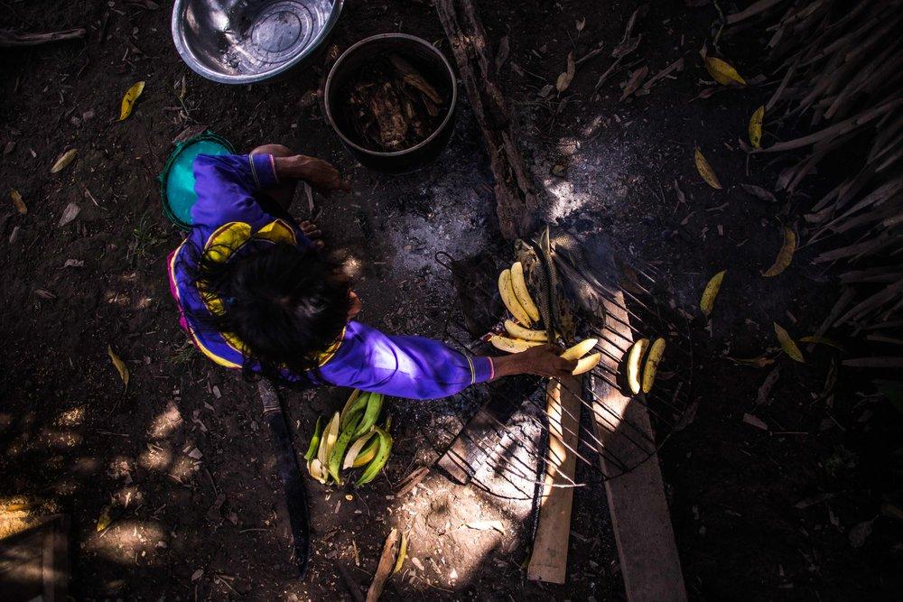 Pekon Rabi prepara un típico almuerzo Shipibo; pescado fresco y plátanos.