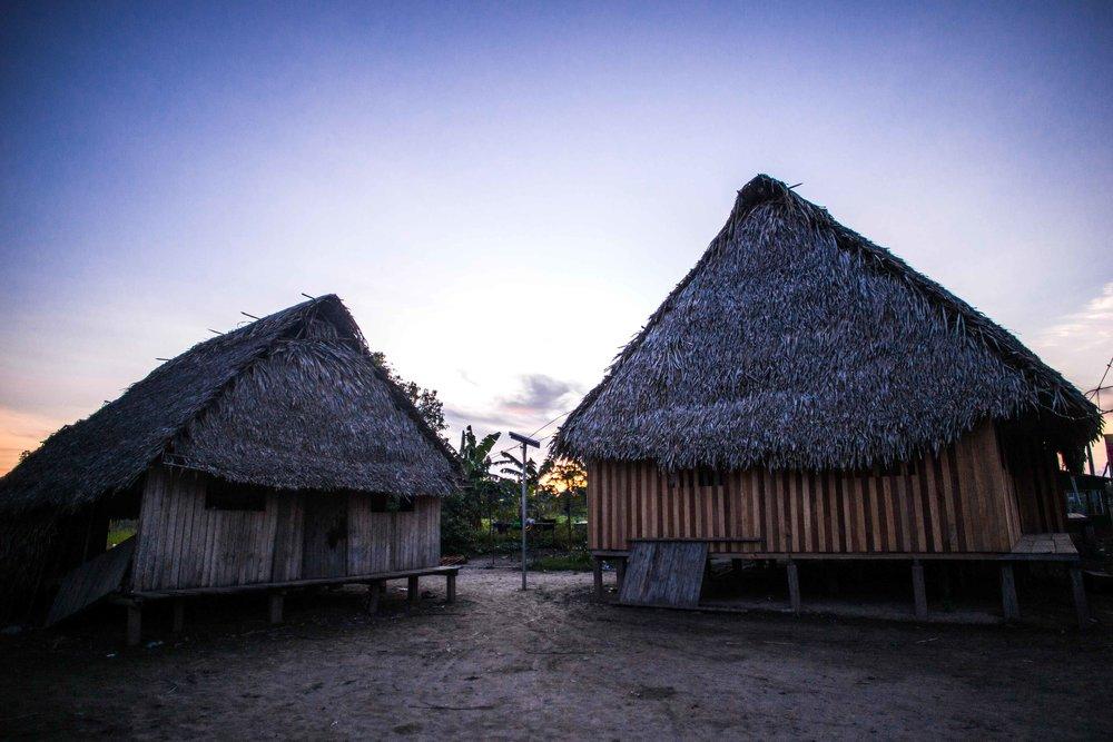 À gauche, l'ancienne maison de Pekon Rabi, aujourd'hui utilisée comme atelier pour son art et comme sorte de salle à manger, à côté de la cuisine. La nouvelle maison a été construite avec l'argent collecté du projet textile et abrite le couchage pour toute la famille.