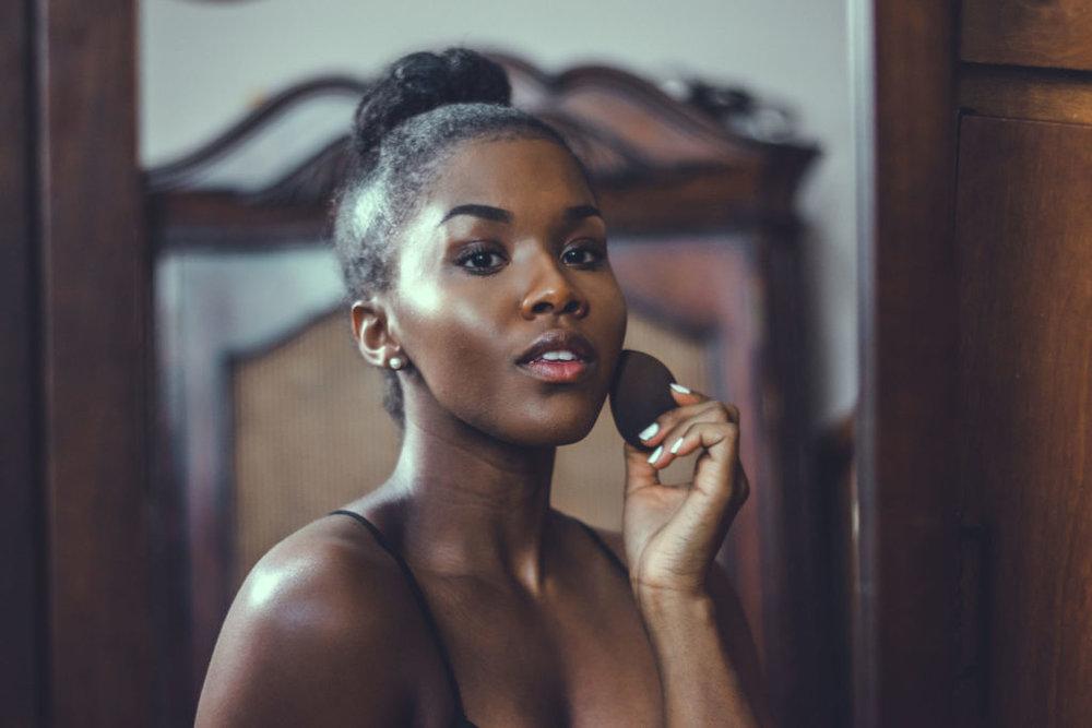 black blogger applying foundation in the mirror