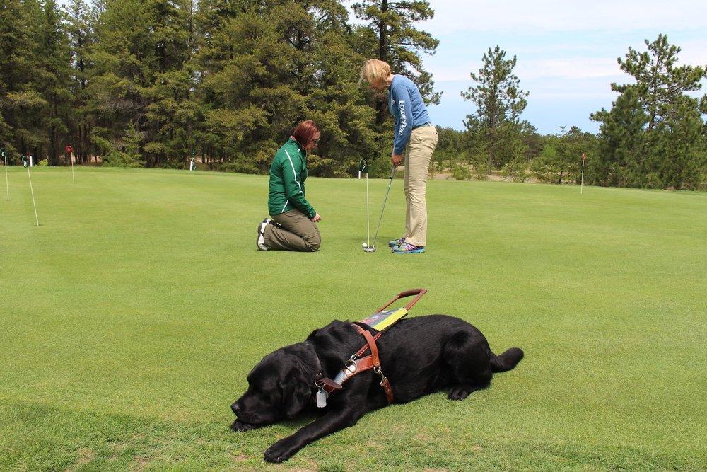 Preston golfing while her Leader dog Floyd enjoys a rest.