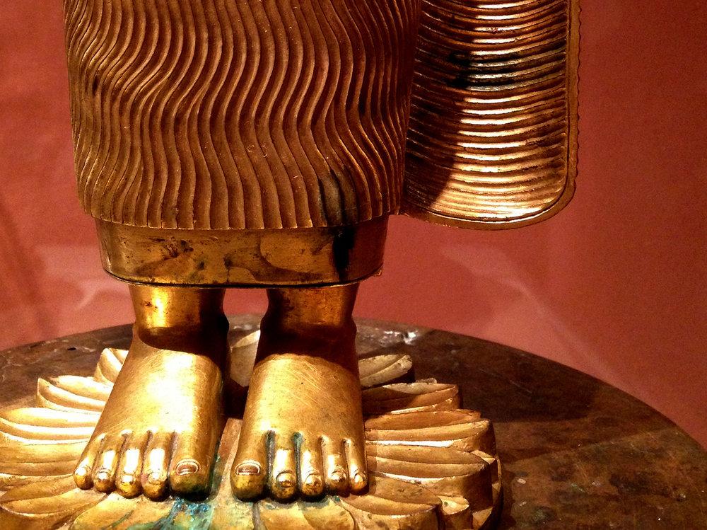 Golden Sri Lankan statue of Buddha standing on a lotus.