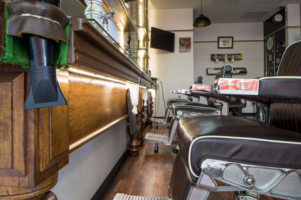 - A damaged hardwood pool table spans the length of the shop, repurposed to serve as the Barbers' triple workstation.