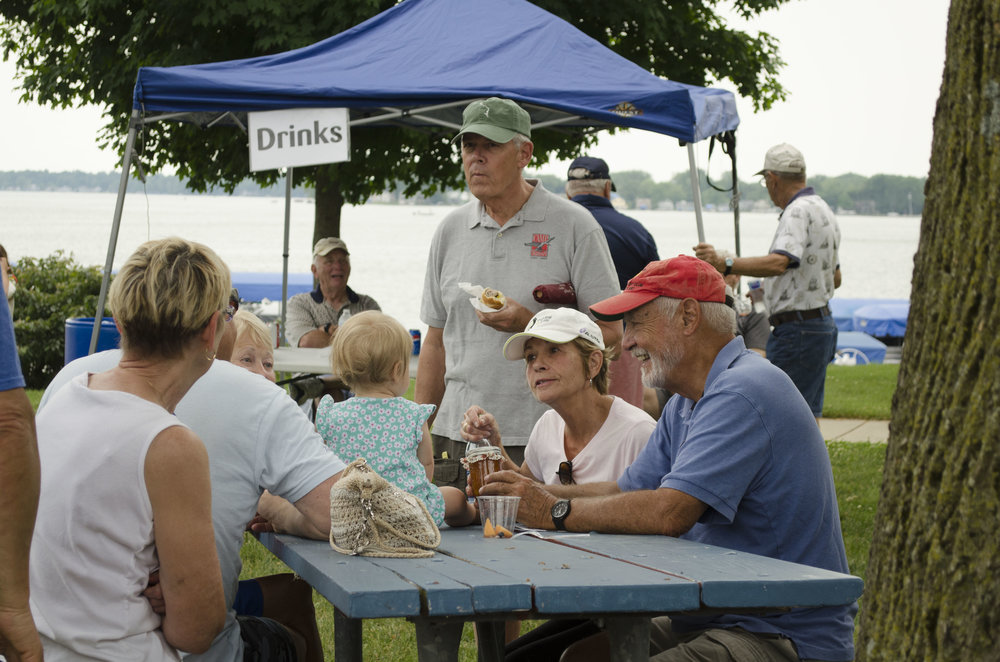 Attendees sit in the park and enjoy food from a variety of vendors.