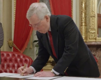 Sen. Mitch McConnell (R - KY) signs the 2018 Farm Bill with a pen crafted from hemp
