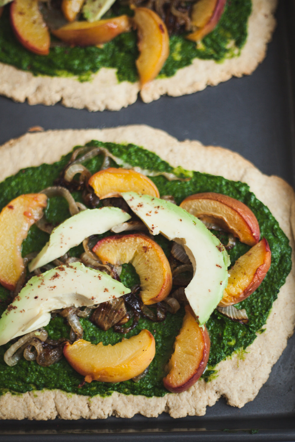 einkorn & oat flatbread w kale pesto, caramelized onions, avocado, peach, & sumac (vegan) via will frolic for food