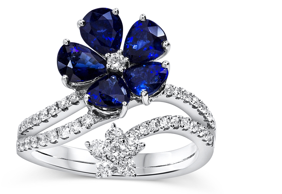 Blue Sapphire and Diamond Flower Ring - Luminous pear shape sapphires serve as petals that bring to life this gorgeous floral motif design.  An expertly crafted 18k white gold split shank embellished with sparkling diamonds; at the tip of the shank is a smaller flower set with round diamonds as well. A beautiful piece to add to anyone's collection.
