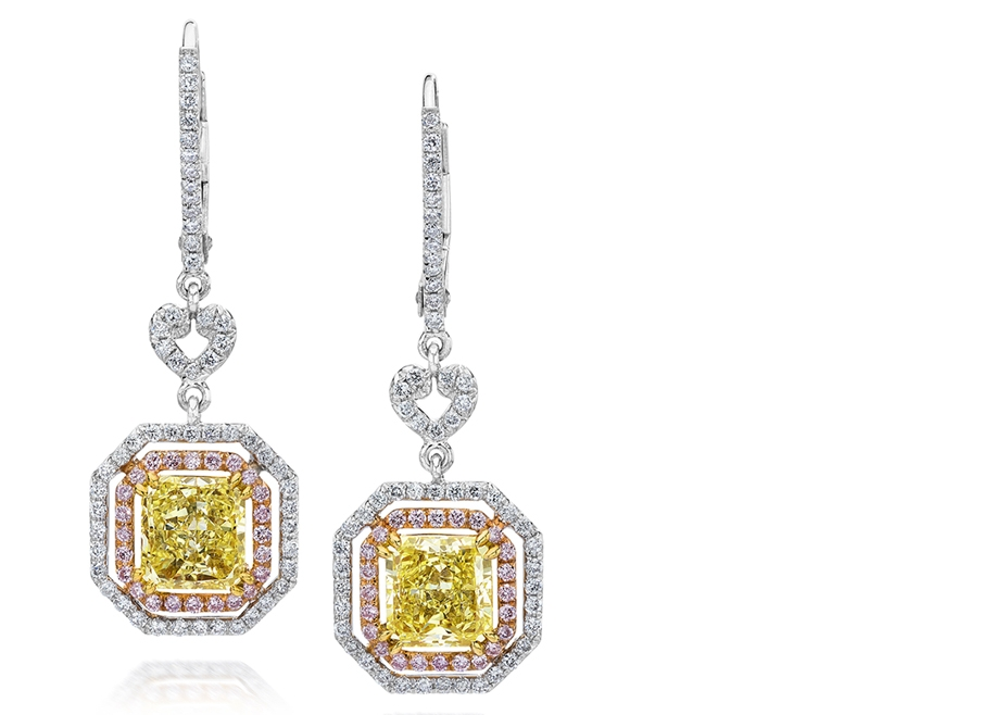 Tri-Color Diamond Halo Dangle Earrings - A colorful pair of earrings. Features a pair of radiant cut fancy yellow diamonds. Surrounded by 2 rows of round brilliant diamonds. The first row set with pink melee diamonds while the second row with white melee diamonds. Spaced by a diamond encrusted open-work heart shape. Suspended on accented lever-backs.