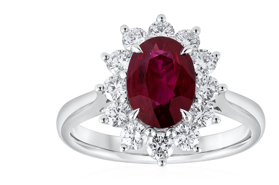 Ruby and Diamond Halo Ring - A gorgeous and vibrant oval ruby bask in the spotlight as it's complimented by a floral design halo set with 12 sparkling diamonds. 18k white gold composition with a comfort fit shank. An absolutely stunning piece.