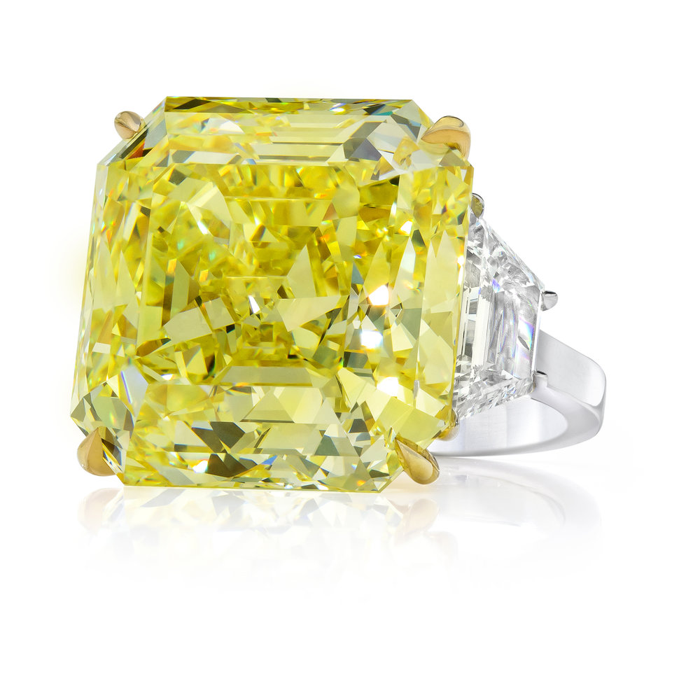 30.02 CARAT FANCY INTENSE YELLOW DIAMOND RING   A very rare piece of jewelry that will catch everyone's eye. Features a stunning 30.02 carat asscher cut diamond that GIA certified as Fancy Intense Yellow (FIY) color and VVS2 clarity. Elegantly set in an 18k yellow gold basket, the center stone is flanked by trapezoid diamond side stones weighing 2.35 carats total. Expertly-crafted in a polished platinum composition. Magnificence at it's finest.