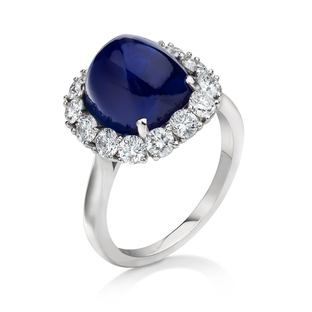 KASHMIR CABOCHON SAPPHIRE HALO COCKTAIL RING   Sapphires from Kashmir are the king of all sapphires because of it's superb near-perfect quality and 'blue velvet' color. This ring features a cabochon Kashmir blue sapphire set in a brilliant diamond surround in 18k white gold. A gorgeous piece for Sapphire enthusiasts.