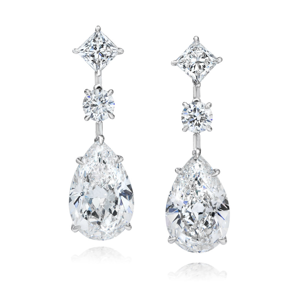 PEAR SHAPE DIAMOND DROP EARRINGS   Bold and elegant. All the diamonds in these earrings are GIA certified. 6.41 and 7.10 carat pear shape diamonds gracefully drop in an everlasting platinum mounting. Each pear shape diamond spaced by a round brilliant diamond (1.18 TCW) and suspended on a princess cut diamond (1.88 TCW) stud.