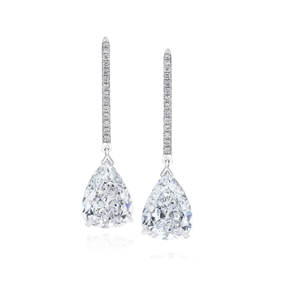 PEAR SHAPE DIAMOND DROP EARRINGS   Accentuate glamour and style with this gorgeous pair; features pear-shape diamonds set in a simple single wire platinum mount accented by small round brilliant diamonds.