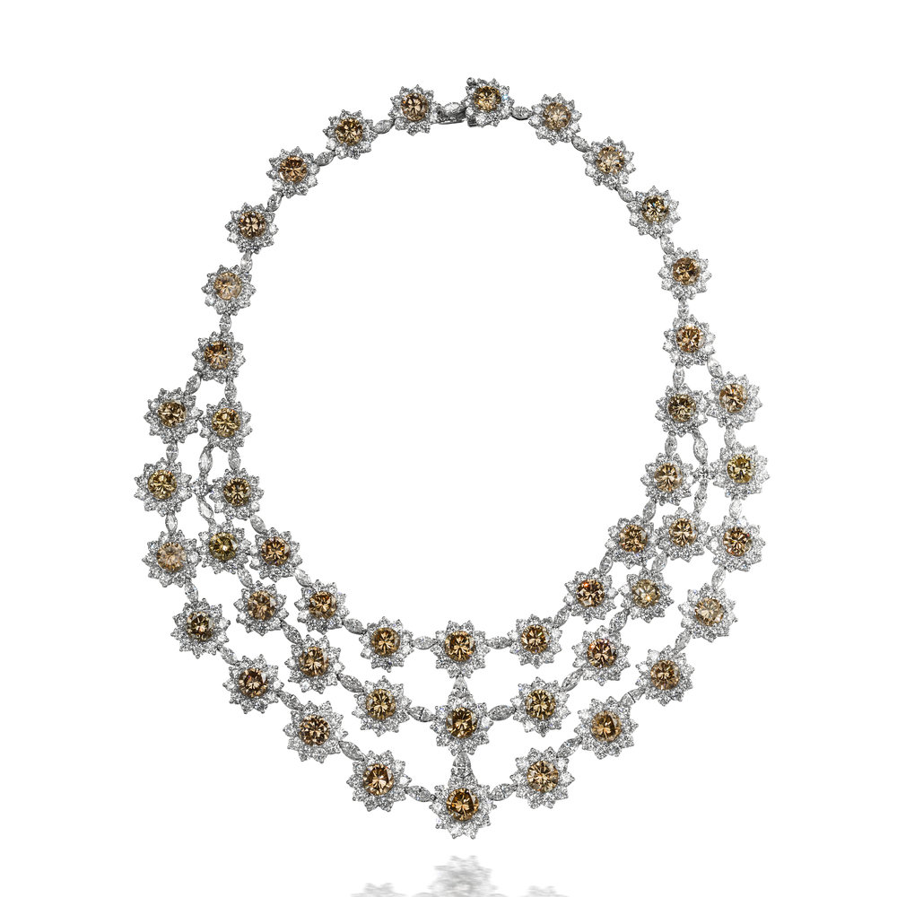 FANCY BROWN DIAMOND FLORAL MOTIF TRIPLE STRAND NECKLACE   A gorgeous piece of jewelry that will definitely catch everyone's eye; features natural round fancy brown diamonds. Each brown diamond surrounded by dazzling round diamonds in a floral motif style and spaced by white marquise diamonds.