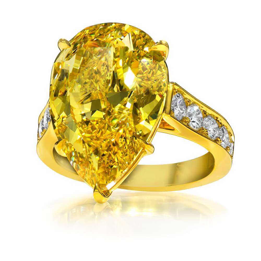 FANCY DEEP YELLOW PEAR SHAPE DIAMOND RING   Set hearts ablaze with this important fancy yellow ring. Showcases a vibrant Fancy Deep Yellow diamond center as radiant as the morning sun. Set in an 18k yellow gold cathedral style setting. The composition encircled by sparkling round diamonds.