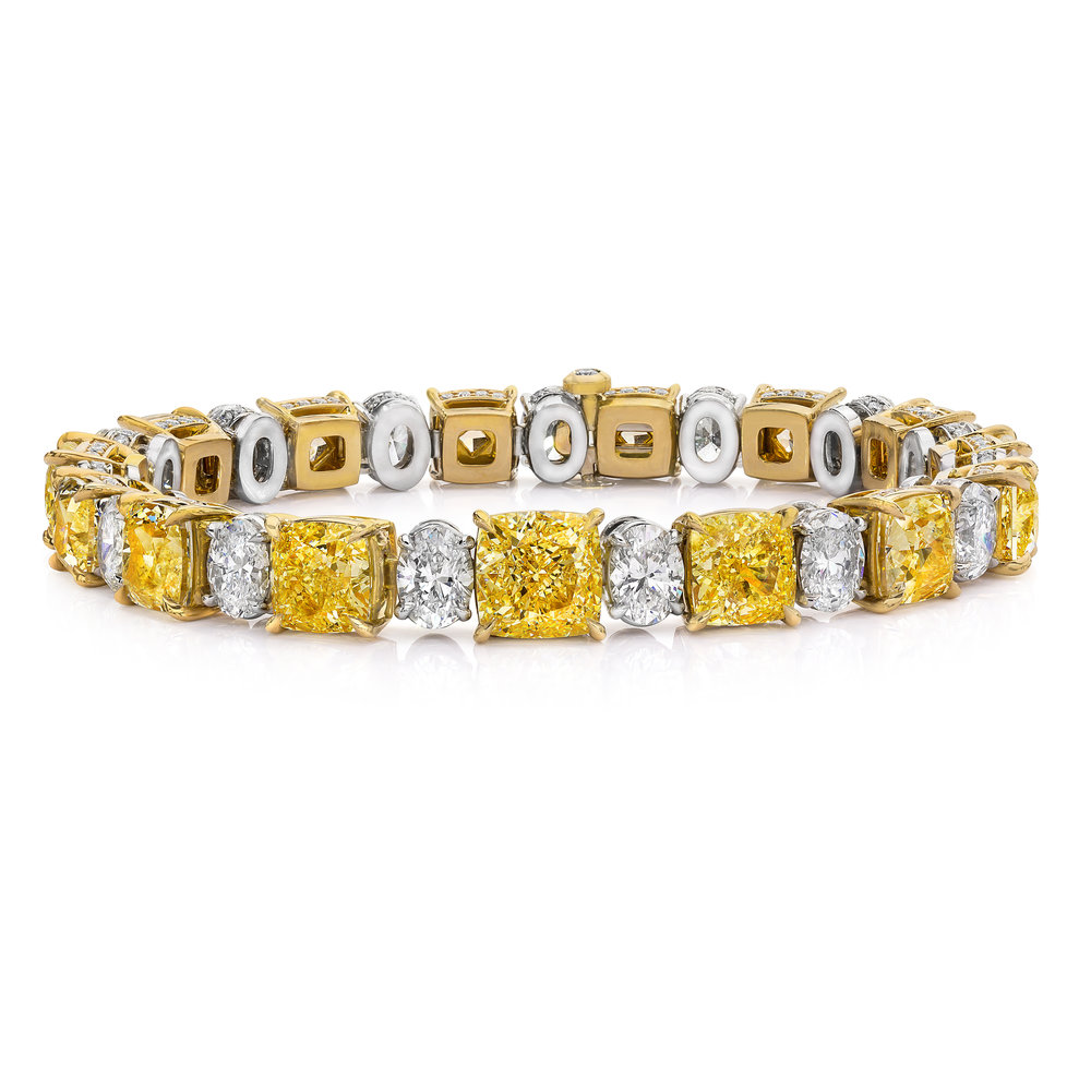 IMPORTANT ALTERNATING FANCY YELLOW AND WHITE DIAMOND TENNIS BRACELET   An absolutely stunning piece for any collector. Features fancy yellow radiant cut diamonds that alternate with sparkling oval cut diamonds securely set in a 4 prong basket made in 18k gold. Each basket is accented by brilliant round diamonds. A magnificent piece part of the Extraordinary Jewelry of the Roman Malakov Collection.