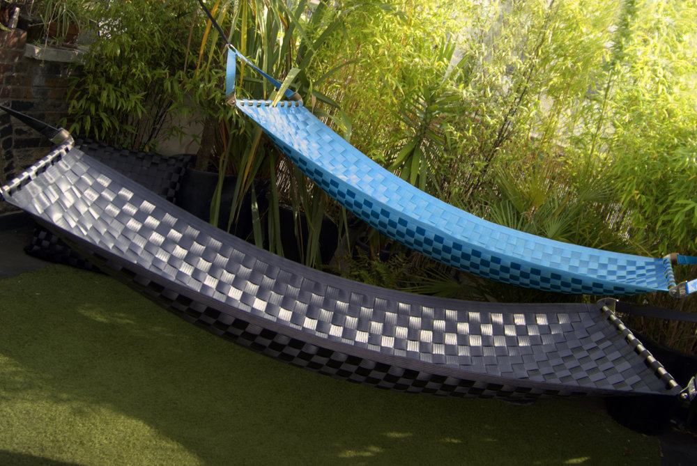 Electric blue and navy blue Ting Sling seatbelt hammocks in an outdoor environment.