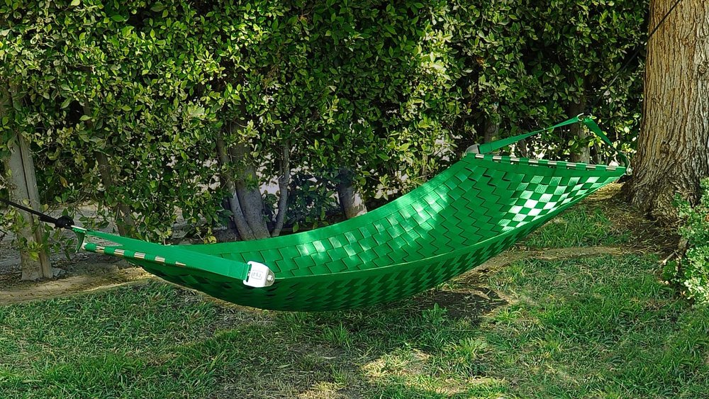 Lime green Ting Sling seatbelt hammock, hanging in the sun surrounded by greenery.