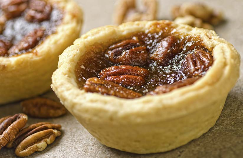 Closeup-photograph-of-pecan-tartlets-and-pecan-nuts-000021956816_Large.jpg