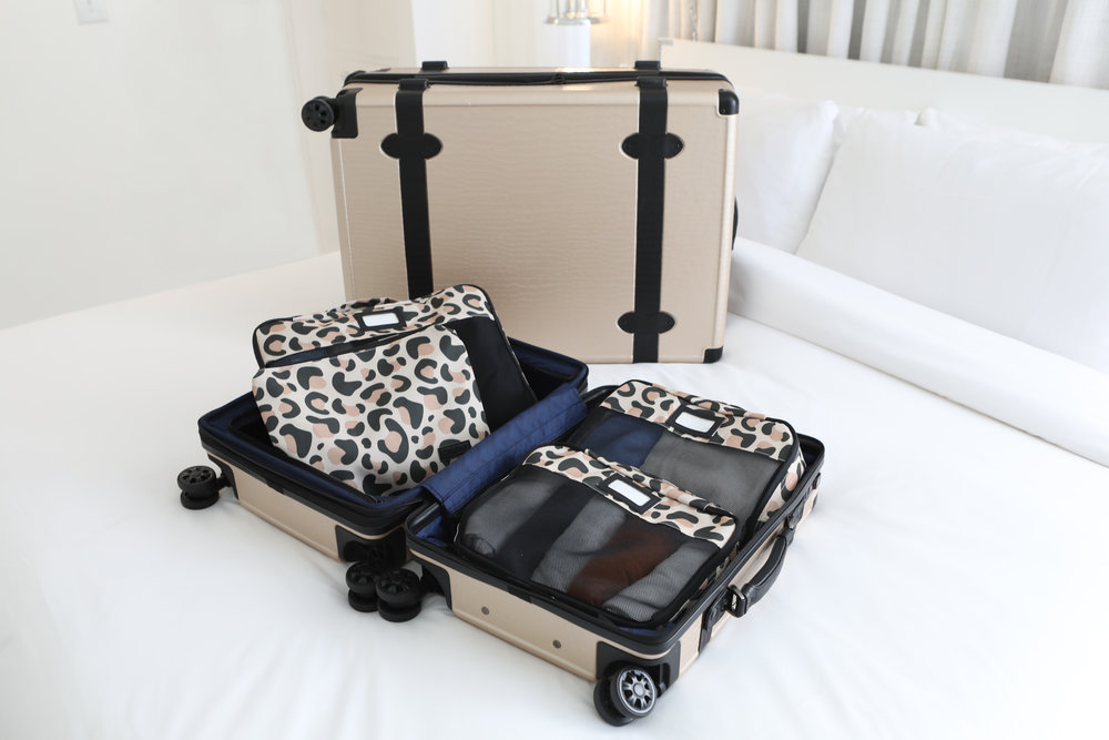 CALPAK's leopard print packing cubes in Trnk carry-on in nude with Large Trnk carry-on in nude on a bed in a hotel room.