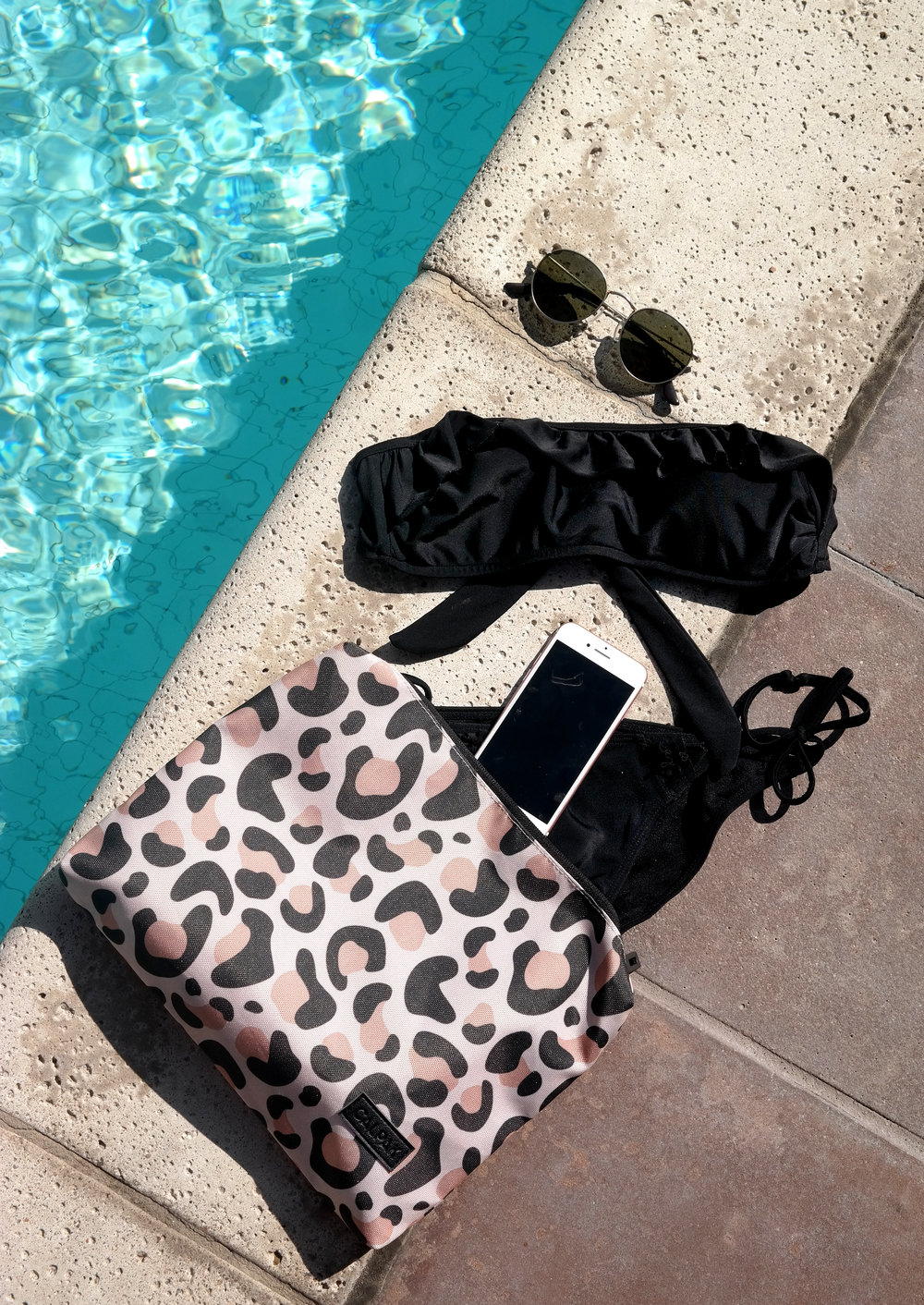 CALPAK's leopard print pouch from packing cubes is waterproof; photographed with swimwear and essentials next to a pool.