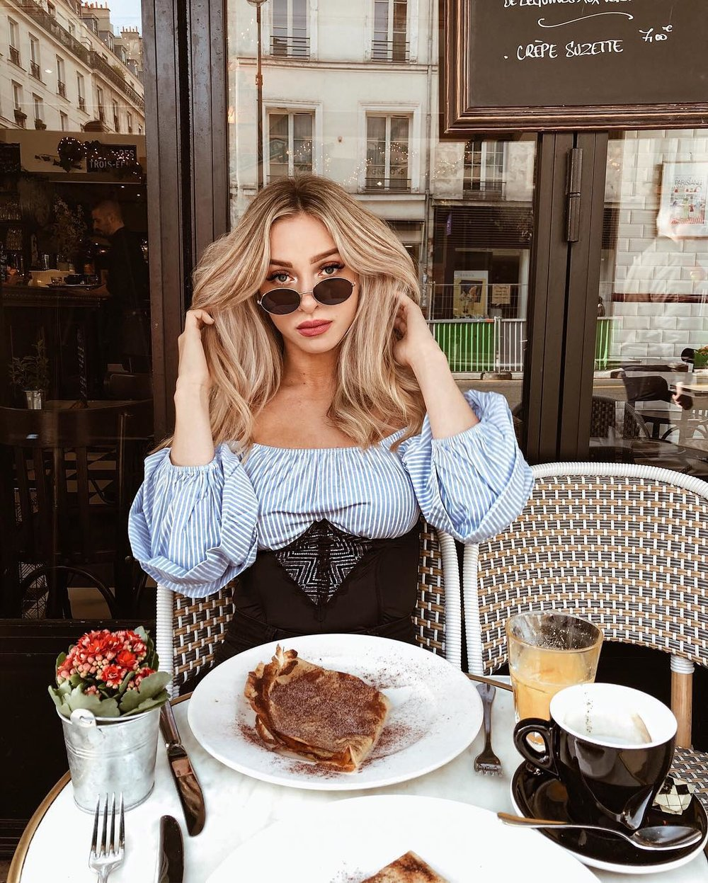 @thestyleseed at a cafe in Paris with a crepe.