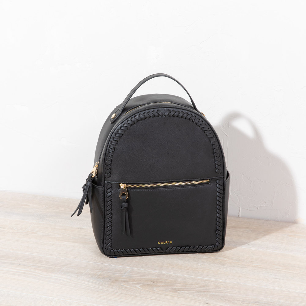 """Kaya Backpack - Black - We like to think of this backpack as the """"I'm going places,"""" backpack. The Kaya backpack is perfect for all the times you have too much stuff for a purse, and too little for rolling luggage. Your water bottle, your ipad, your mid-day snack, your headphones, and more, will all fit neatly and sweetly in this travel BFF."""