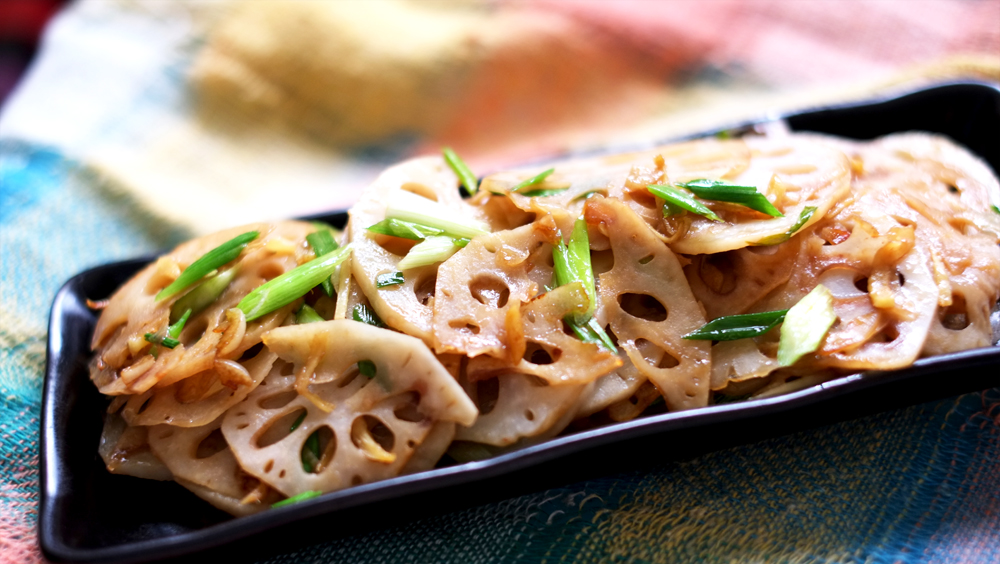 Sauteed Lotus Root   Prep time: 10 mins  Cook time: 5 mins  Total time: 15 mins  Serves: 4      Ingredients:   · 1 segment of Lotus root  · a knob of Ginger  · 3 cloves of Garlic  · 2-3 bunches of Spring onions  · 1 tablespoon Soy sauce  · 1 teaspoon Sugar  · 1 tablespoon Vegetable oil  · 1 tablespoon Sesame oil  · 1 tablespoon of Vinegar mixed in a large bowl of water     Instructions:  1) Slice the lotus root as thinly as you possibly can and as you do that, toss  each slice into the bowl of vinegar water, this prevents the lotus roots from  oxidizing.  2) Next, remove the skin of the ginger and cut it into thin slices.  3) Mince the garlic up as well.  4) Lastly, we will only use about 3 inches of the spring onion from the root side  (the white part), the green segment can be kept in the fridge. Cut off and  discard the bulb of the spring onion and slice the rest at an angle.  5) Heat up the vegetable oil in a skillet, throw in the ginger and garlic when  the pan is hot enough, and move them around for about 20-30 seconds  until the lovely fragrance is released and before they burn.  6) Now add the spring onions and lotus root, turning the fire down to medium  as you do.  7) At this time, you should find that there is very little oil in the pan, so throw in  the tablespoon of Sesame oil.  8) Continue to sauté all the ingredients in the pan for about a minute before  adding the soy sauce and sugar.  9) Toss everything together to evenly coat the ingredients with the soy sauce.  10) When the lotus root slices have taken on a beautiful golden caramelized  hue, turn the fire off and serve!