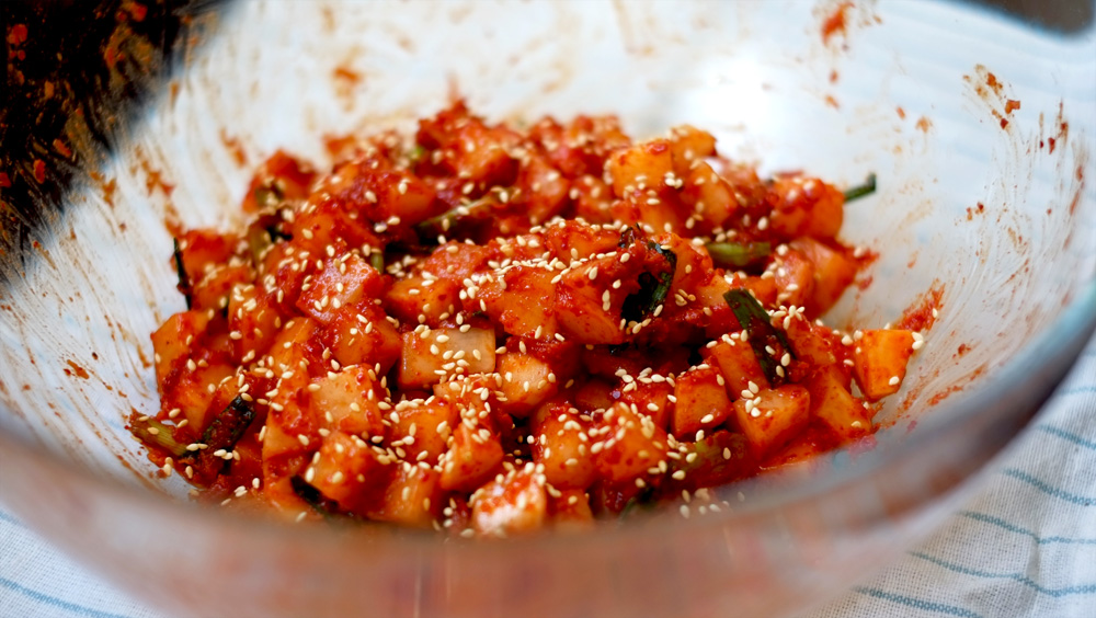 Radish Kimchi   Prep time: 10 mins  Total time: 10 mins  Serves: 10-12     Ingredients:   · 1 medium Radish, cut into small cubes  · ½ Asian Pear, grated (use Pear Juice if you can't find this fruit)  · 6-8 cloves Garlic, grated  · 2-inch knob fresh Ginger, grated  · 2 stalks Spring Onion, cut into 2-inch strips  · ½ cup Chilli Pepper Flakes  · 3-4 tablespoons Fish Sauce  · 2 tablespoons Sugar  · 3 tablespoons Sesame Oil  · 1/8 cup Toasted Sesame Seeds    Instructions:  1) Place the cubed radish in a large mixing bowl.  2) Mix all the other ingredients, except the sesame seeds, in a separate bowl,  combining thoroughly to create the seasoning paste.  3) Pour the seasoning paste into the bowl with the radish cubes and toss   the radish (with your gloved hand!) to coat thoroughly with the seasoning  paste.  4) Sprinkle the sesame seeds over the radish kimchi and transfer kimchi   into an airtight container to store in the fridge.