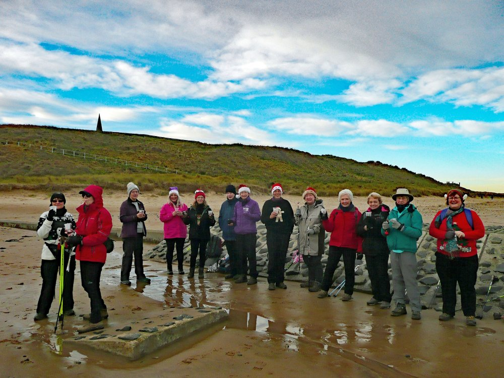 Nordic Walking session wearing santa hats on Saltburn sandy beach at Christmas 2017 with blue sky and clouds