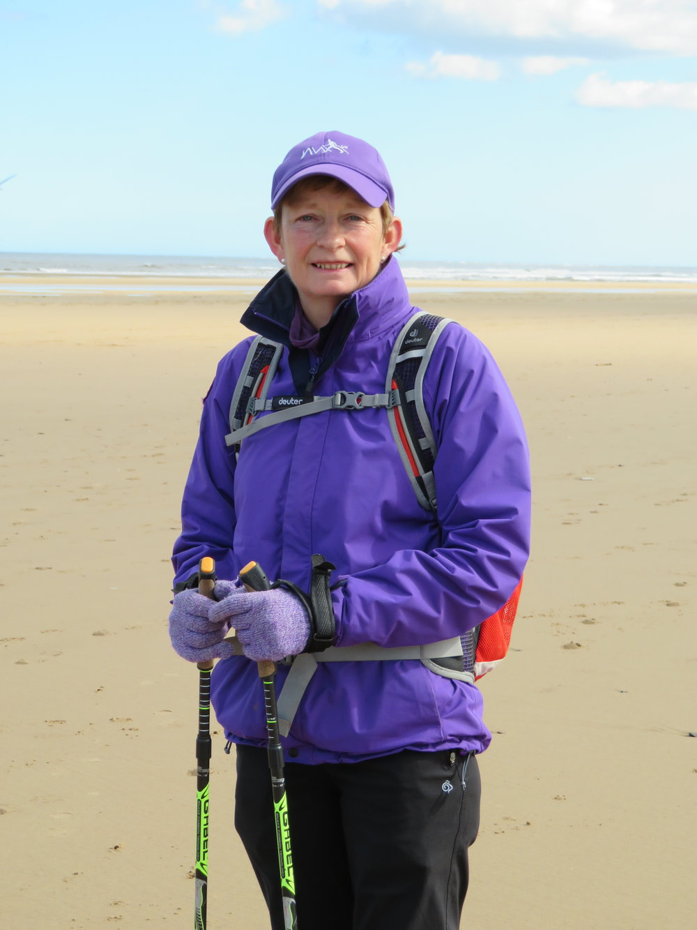 Pat is dressed in dark purple jacket and purple cap, tightly holding Nordic walking poles to her on a large sandy beach with tide in the distance with a light blue sky.