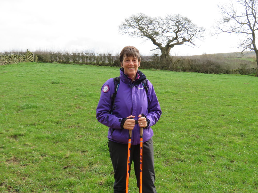 Jo is dressed in dark purple jacket and purple cap, tightly holding a pair of orangeNordic walking poles in a green field with large oak tree and hedge behind.