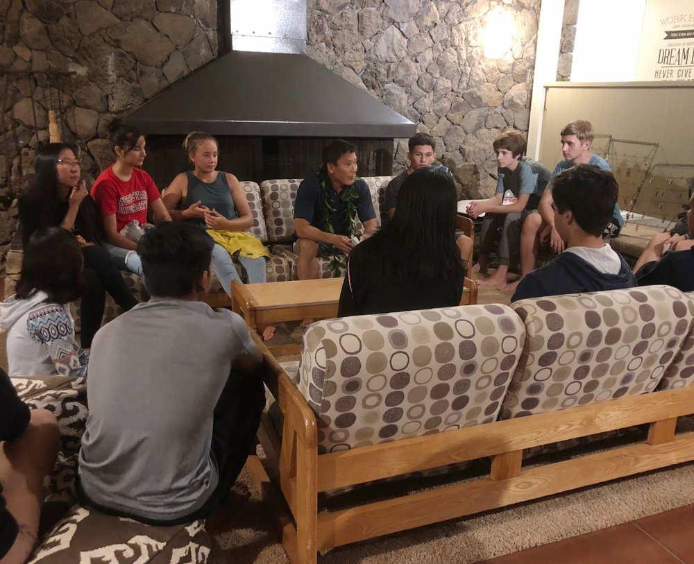 Nalukai 2018 campers sit in a circle with executive coach Warren Doi for a fireside chat. Photo by Aaron Schorn.