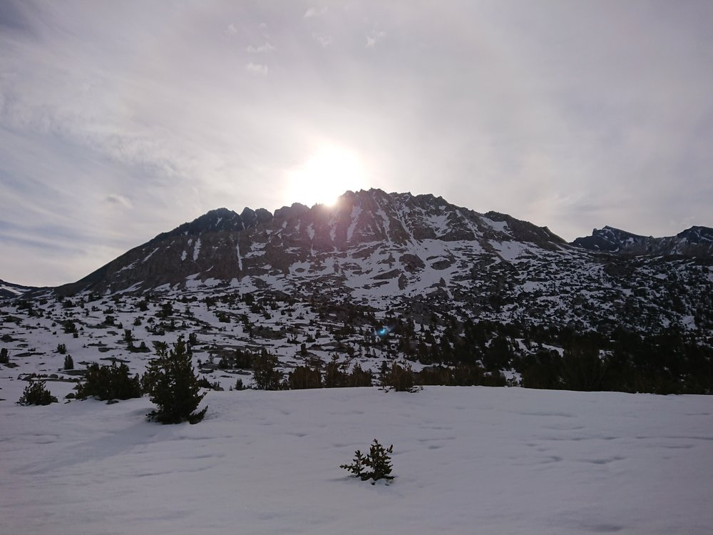 The sun is starting to show itself behind the surrounding mountains.