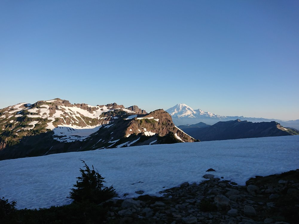 Mount Rainier in distance with a snow covered high mountain lake in the foreground