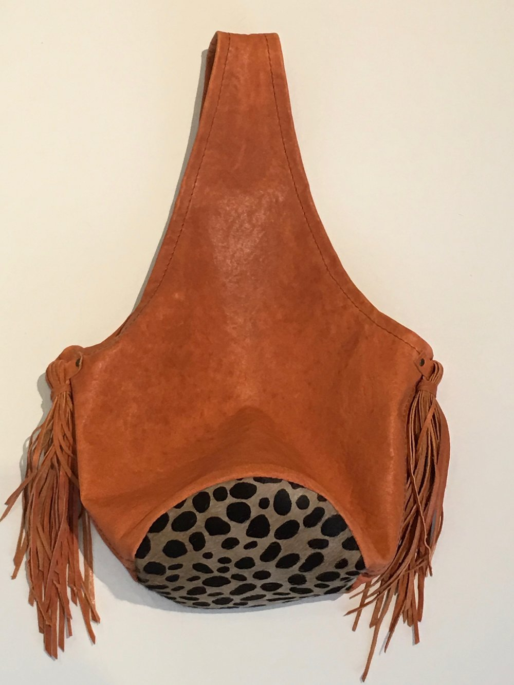 Coral lambskin Bucket Style Bag with hair on hide bottom and long soft lambskin tassels.  $275..jpg