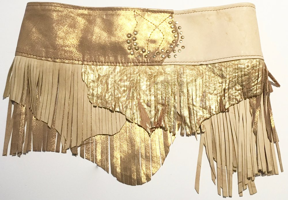 Light tan and metallic gold lambskin.  Layered fringe and gold colored stud work. Coconut ring with adjustable velcro closure. Back view.jpg