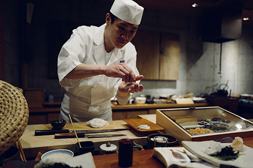 asian chef making sushi in restaurant