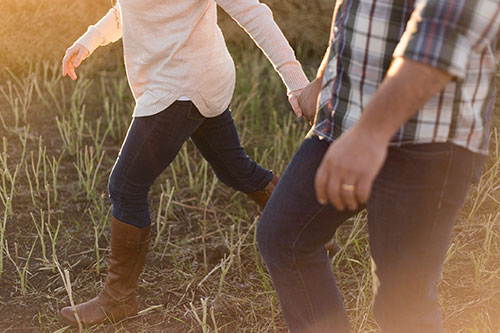 Close up of couple holding hands in a field