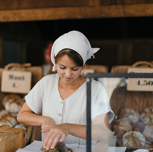 female baker cutting bread in store