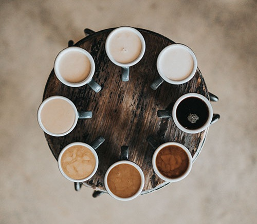 Group of eight types of teas laid out on a wooden table in a perfect circle